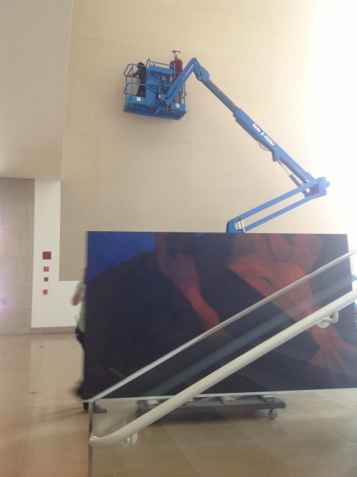 DMA staff vacuuming the Atrium wall in preparation for Tamayo's painting.
