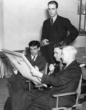 "Richard Foster Howard (standing) with jurors Xavier Gonzales, Donald Bear, and Frederick Browne judging the Texas section of the ""Greater Texas and Pan-American Exposition,"" 1937"