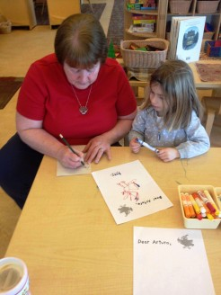 """Here is one of the children working with a teacher on her letter to Arturo. She asked about spelling and punctuation. She wanted to know if Arturo is friends with Amelia and if he is her friend, too."""