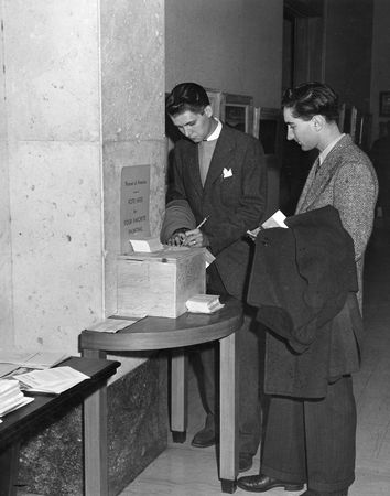 "Young men voting for their favorite work in the exhibition ""Portrait of America,"" September 30-November 5, 1945 (Photograph from the Studio of Wm. Langley)"