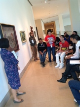 Miguel sharing his narrative response to Leonora Carrington's surrealist painting on Level 4.