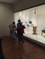 Two participants look closely at objects in the gallery.