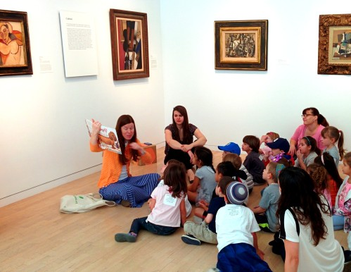 Leah Hanson, Manager of Early Learning Programs, reads a story to Pre-K children in the galleries.