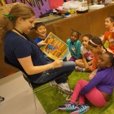 Mary reads a story to campers during snack time.